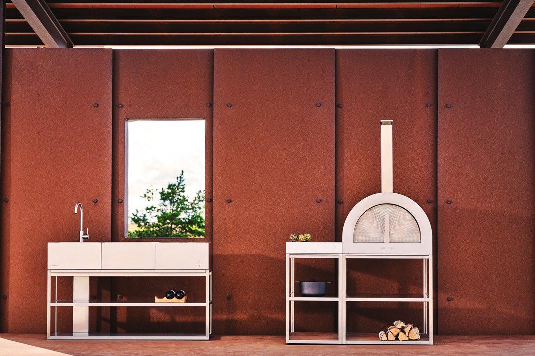 Outdoor Küche in skandinavischem Design vor einer roten Außenwand.
