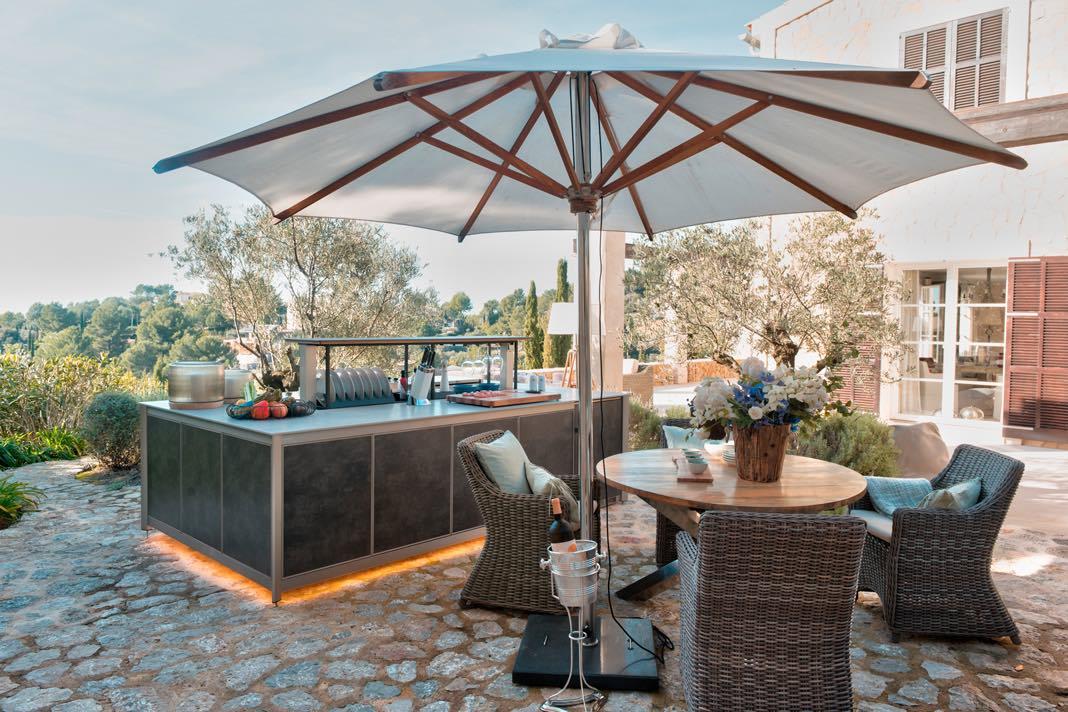 Outdoor Küche vor einem romantischen Landhaus mit Sonnenschirm.