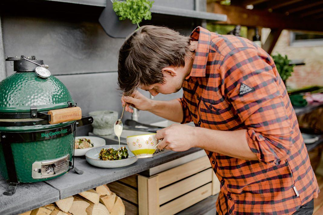 Mann bereitet Marinde in einer Outdoor Küche zu.