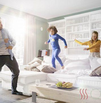 Glückliche Familie im Wohnzimmer ihres Hauses mit Raumklima-Systemlösung