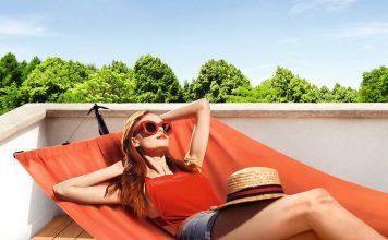 Frau liegt in einer Hängematte und sonnst sich am Pool.