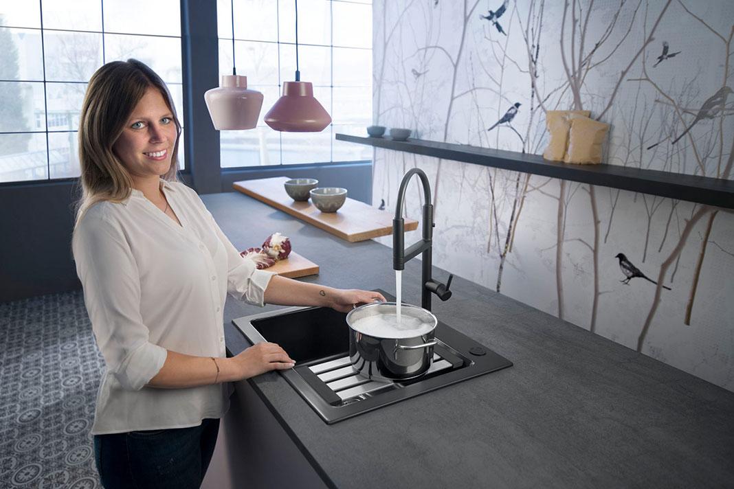 Frau nutzt Armatur in der Wohnküche mit Cold-Start-Technologie