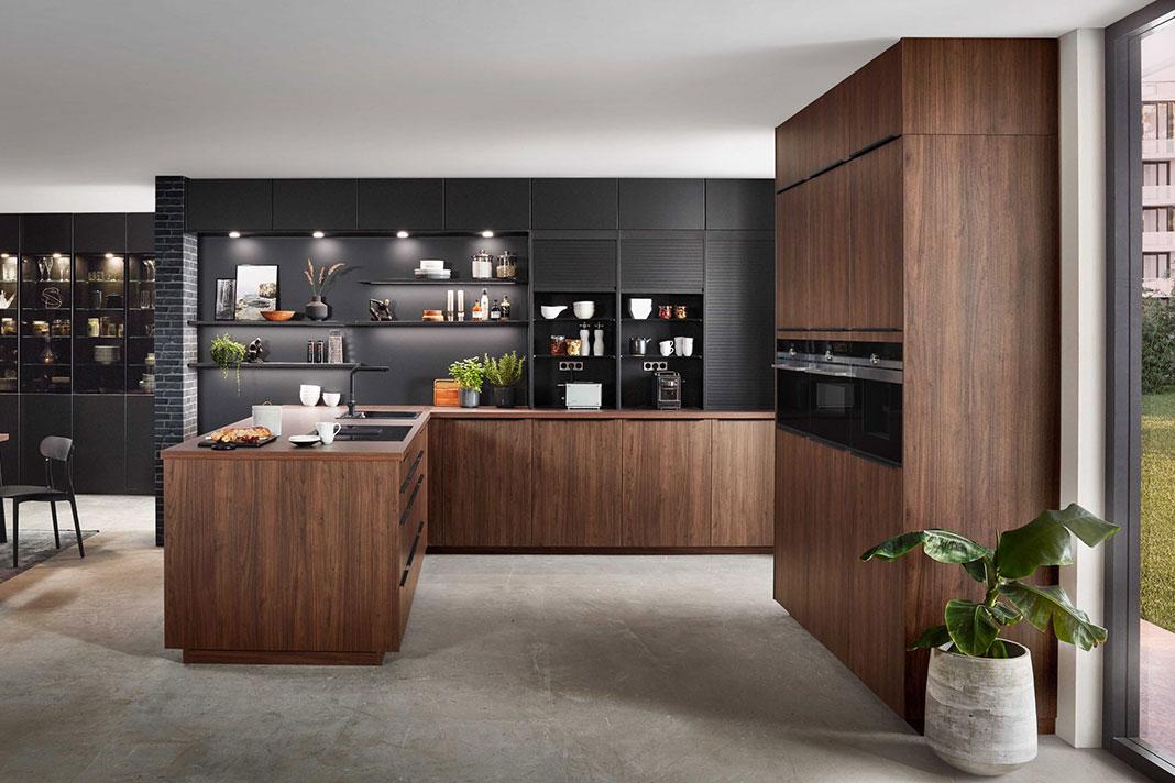 Wohnküche mit Küchenelementen in Holzoptik und Schrankelementen in matt Schwarz