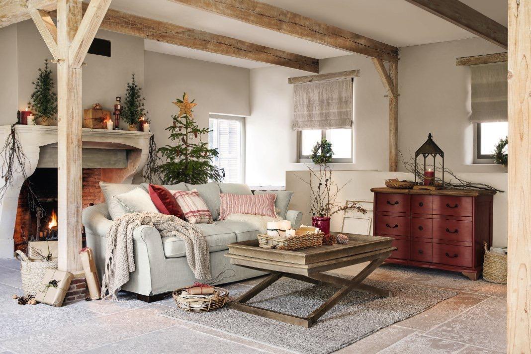 Weihnachtlich dekoriertes Wohnzimmer im amerikanischen Landhausstil mit Decken, Kissen und einem Kamin.