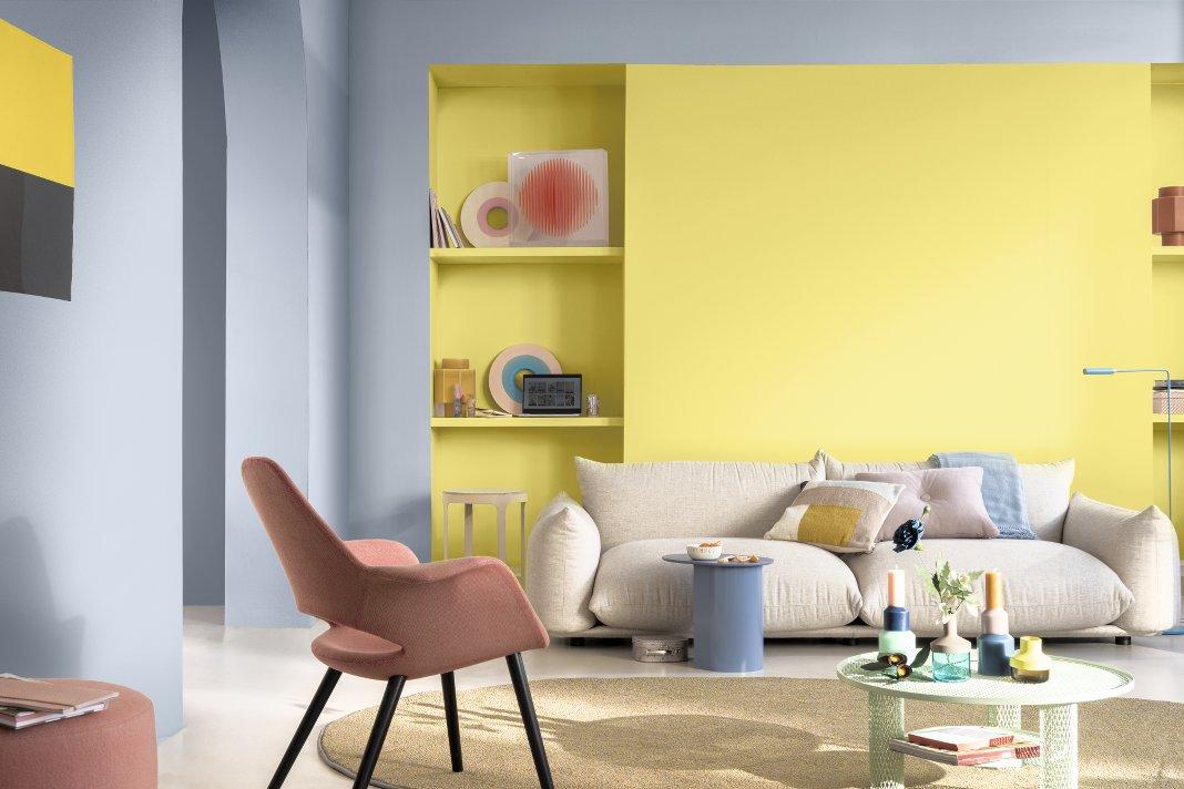 Wohnzimmer mit gelber und blauer Wand.
