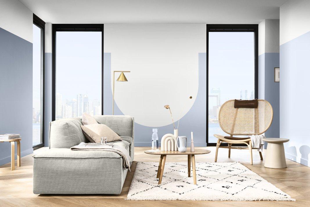 Helles Wohnzimmer mit hellblauen Wänden und bodentiefen Fenstern mit Blick auf Wolkenkratzer.