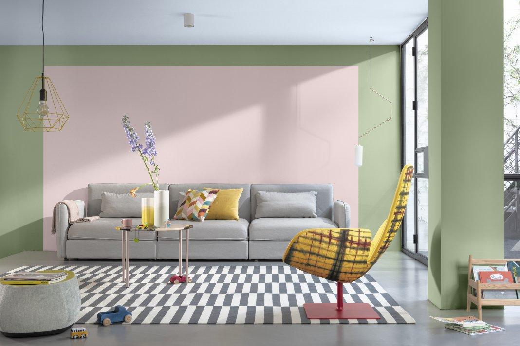 Wohnzimmer mit Sofa vor einer rosa und grün gestrichenen Wand.